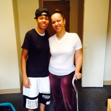 pic of daughter and me standing together in her dorm room. She's wearing black t-shirt and shorts with a hat turned backwards. I'm wearing white t-shirt and brown sweatpants while holding onto cane.